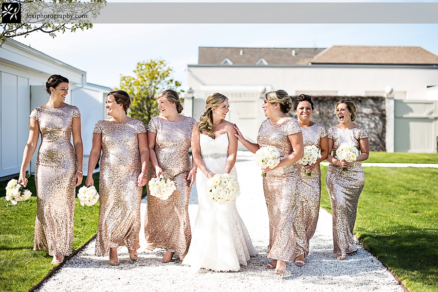 bride and bridesmaids wearing gold sequin badgley mischka dresses walking and laughing outside the belle mer island house