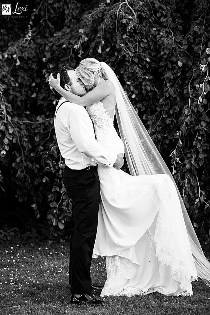 black and white photo of the groom lifting the bride and kissing her
