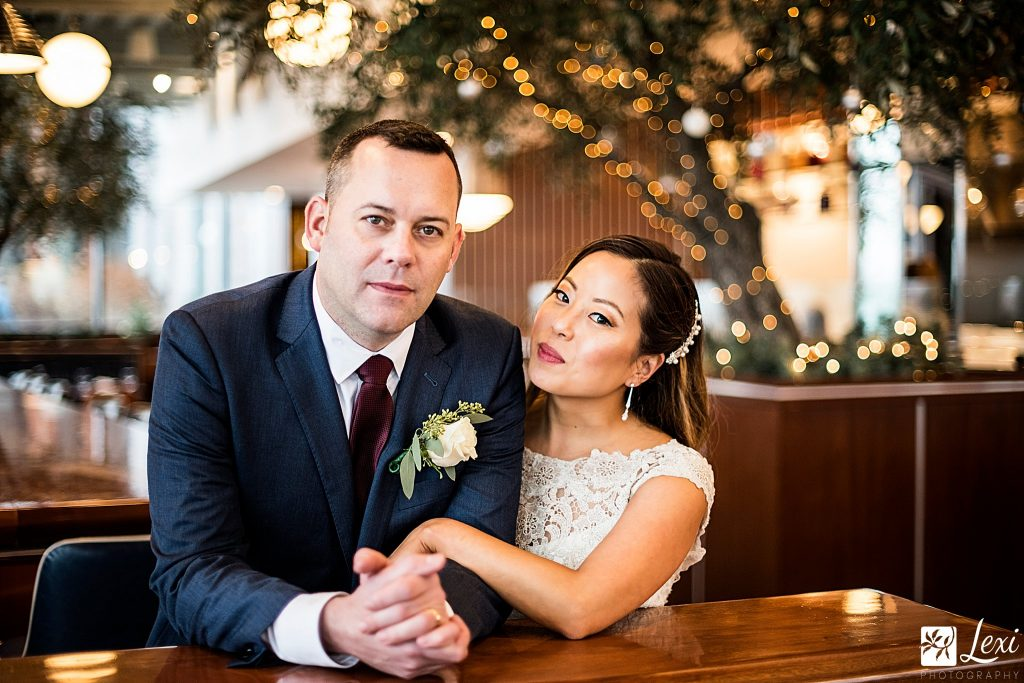bride and groom inside a restaurant with twinkling lights behind them